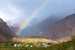 Rainbow over the village in the mountains. Landscape Royalty Free Stock Photo