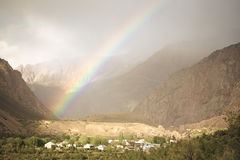 Rainbow over the village in the mountains. Landscape. Toned Stock Photo