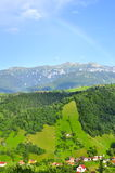 Rainbow over village  Romania Bucegi  mountains Stock Photo