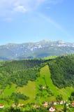 Rainbow over village  Romania Bucegi  mountains. Rainbow over the beautiful village of Bran Moeciu village  Romania with Bucegi montains landscape Stock Photo