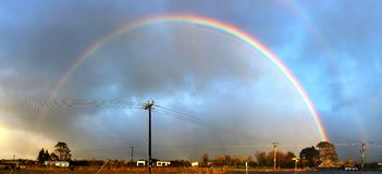 Rainbow over a village in Taranaki National Park Royalty Free Stock Photography