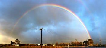 Rainbow over a village in Taranaki National Park. Double colourful rainbow over a village in Taranaki National Park in New Zealand Royalty Free Stock Photography