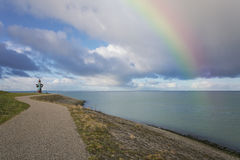 Rainbow over the water. A bicycle trail lined along the shore of the river mouth. Monument dedicated to the flood occurred in the province Royalty Free Stock Images