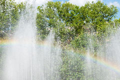 Rainbow over water in fountain with green trees on background. Defocused Royalty Free Stock Photos