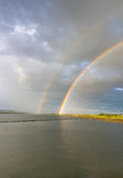 Rainbow over water Stock Images