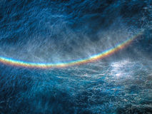 Rainbow over water... A shot of a rainbow formed over splashes of water Stock Photo