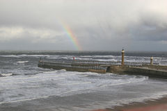 Rainbow over Whitby Harbour piers. Stock Image