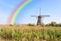 Rainbow over the Windmill at Kinderdijk. Water Reflexion over the Windmill and the landlord house at Kinderdijk listed in the UNESCO heritage list Stock Photos