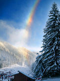 Rainbow over wintry landscape. Scenic view of colorful rainbow over forested mountainside and ski slope, winter scene stock images