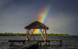 Rainbow over wooden pier Stock Photo