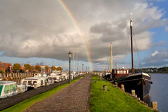 Rainbow over Zoutkamp haven with boats Stock Images