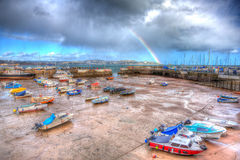 Rainbow at Paignton harbour Devon England uk in colourful HDR with boats and view to Torquay Royalty Free Stock Photos