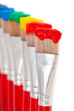 Rainbow paint colors. Artist's paintbrushes holding all seven colors of the rainbow - red, orange, yellow, green, blue, indigo and violet royalty free stock photography