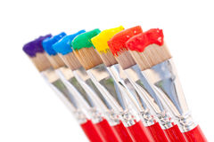Rainbow paint colors. Artist's paintbrushes holding all seven colors of the rainbow - red, orange, yellow, green, blue, indigo and violet Stock Image