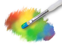 Rainbow Paint Splatter Texture with Paintbrush. A paintbrush is painting a rainbow palette spot. The paint splatter has rough edges Stock Photography