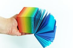 Rainbow paper. Rainbow-hued cards kept in hand Stock Photography