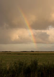 Rainbow. Partial rainbow over grass land near Tonder, Denmark stock photo