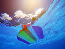 Rainbow pattern styrofoam swimming board floating in poolside wa. Rainbow pattern styrofoam swimming board or baseboard floating in swimming pool water royalty free stock photography