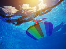 Rainbow pattern styrofoam swimming board floating in poolside wa. Rainbow pattern styrofoam swimming board or baseboard floating in swimming pool water stock images