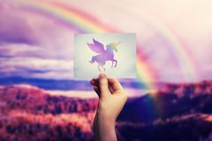 Rainbow pegasus. Woman hand holding a paper sheet with pegasus unicorn icon over wild nature valley background over the rainbow. Love travel and freedom concept stock images