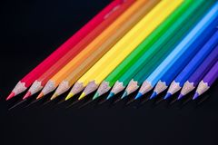 Rainbow pencil colors arranged diagonally on a black glass royalty free stock image