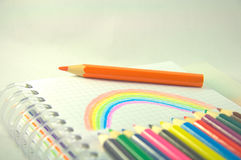 Rainbow and pencils. Twelve colored pencils over white and rainbow Stock Photography