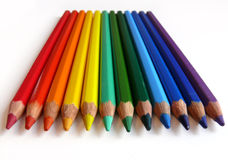 Rainbow pencils. Rainbow colored pencils lying on white paper Stock Images
