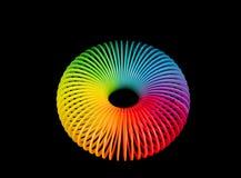 Rainbow plastic spring on black background. Toroid - mathematical, geometric shape over black Stock Photo