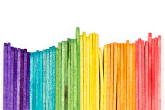 Rainbow popsicle sticks on edge. Multi colored popsicle craft sticks lined up on edge over white stock images