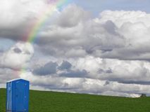 Portable toilet at the end of rainbow Stock Image