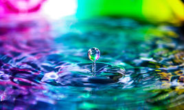 Rainbow Pride Water Drop Splash. All the colors of a gay pride rainbow and bright highlights reflect onto a pool of pure water with one single drop of water royalty free stock photography