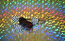 Rainbow racecar darts. Checkered and black and red darts on a rainblow background Royalty Free Stock Image