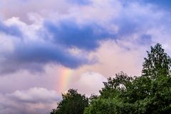 Rainbow after rain in a cloudy sky among dramatic clouds stock photo