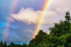 Rainbow after rain in a cloudy sky among dramatic clouds royalty free stock images
