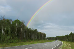 Rainbow after rain over highway Royalty Free Stock Photo