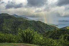 rainbow and rain over the jungle and mountains of mahé, seychelles 11 stock images