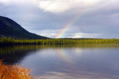 Rainbow after the rain over the northern lake Stock Photos