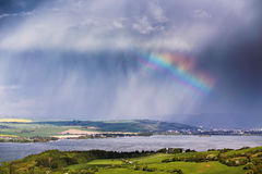 Rainbow after rain. Spring rain and storm in mountains. Royalty Free Stock Image
