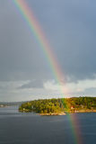 Rainbow in rain during sunshine in sea Royalty Free Stock Images