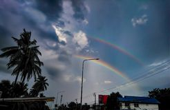 A rainbow after the rain, the two overlap. royalty free stock photo