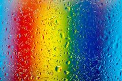 Rainbow raindrops. Rain drops with a rainbow background stock image