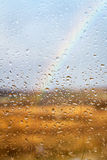 Rainbow through rained window background. Rainbow through rained window with droplets Royalty Free Stock Image