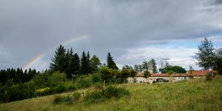 A rainbow after the rains. A rainbow appeares after a rain shower in the idyllic landscape of the French Auvergne. It is a view of a old Chateau located at the stock images