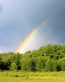 Rainbow in the rainy sky background. Rainbow, coming from the forest and disappearing into the storm cloud Royalty Free Stock Images
