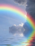 Rainbow reflection. Rainbow reflected in ocean against a background of clouds Royalty Free Stock Image
