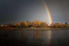 Rainbow with reflection in the lake and the village house. From above Royalty Free Stock Photos