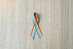 Rainbow ribbon awareness for LGBT and homosexual community pride. Rainbow ribbon awareness on wooden background for LGBT and homosexual community pride concept stock photo