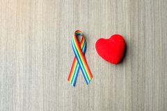 Rainbow ribbon awareness for LGBT and homosexual community pride. Rainbow ribbon awareness on wooden background for LGBT and homosexual community pride concept royalty free stock image