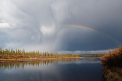 Rainbow on the river in the summer. In Yakutia Royalty Free Stock Photography