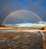 Rainbow with rock in foreground Royalty Free Stock Image